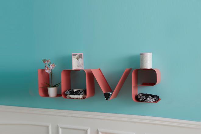Mensola a lettere LOVE di colore rosa su una parete azzurra